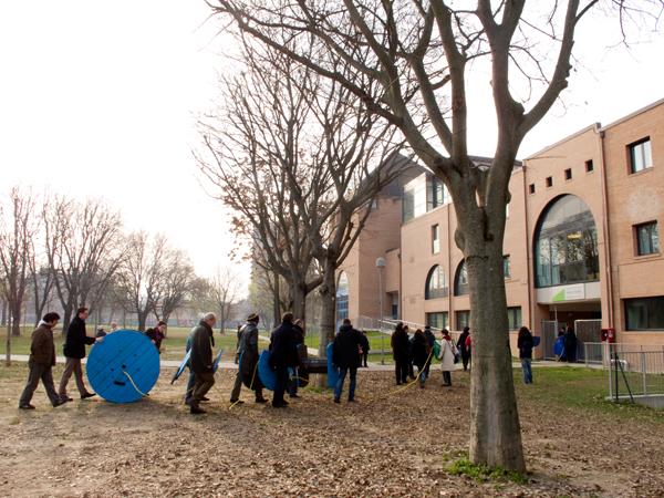 Alcuni abitanti del quartiere partecipano allo spostamento dell'opera d'arte pubblica di Enrico Vezzi
