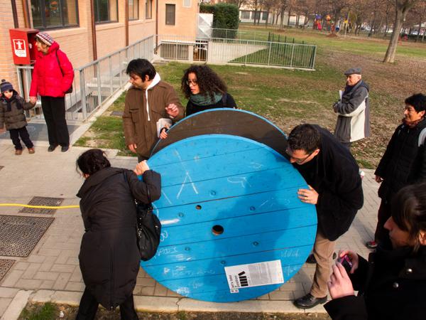 Alcuni abitanti del quartiere partecipano allo spostamento dell'opera all'interno del Centro Zonarelli